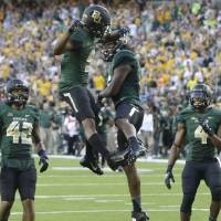 Photo - Baylor wide receiver KD Cannon (9) celebrates his touchdown catch with teammate Davion Hall (16) as Levi Norwood (42) and Jay Lee (4) look on during the first half of an NCAA college football game against SMU Sunday, Aug. 31, 2014, in Waco, Texas. (AP Photo/LM Otero)