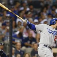 Photo - Los Angeles Dodgers' Adrian Gonzalez watches his solo home run blast head for the right field seats in the sixth inning of a baseball game against the San Diego Padres Saturday, Aug. 30, 2014, in San Diego.  (AP Photo/Lenny Ignelzi)