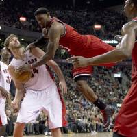 Photo - Miami Heat forward LeBron James, right, falls to the floor after trying to dunk over Toronto Raptors center Aaron Gray, left, during first half NBA action in Toronto on Sunday Feb. 3, 2013. (AP Photo/THE CANADIAN PRESS,Frank Gunn)