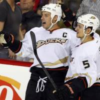 Photo - Anaheim Ducks' Ryan Getzlaf, left, celebrates his winning goal with Luca Sbisa, of Italy, against the Calgary Flames during the third period of their NHL hockey game, Monday, Jan. 21, 2013, in Calgary, Alberta. The Ducks won 5-4. (AP Photo/The Canadian Press, Jeff McIntosh)