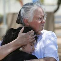 Photo - Marsha Livingston, right, comforts a grieving Kristen Williams, both parishioners at Mother of Mercy church, as they stand outside the church on Thursday, June 12, 2014, in Phoenix, after a Wednesday evening attack left a priest shot and killed and another injured at the Roman Catholic church.  Police have no suspects at this point, but they are canvassing the neighborhood and going over physical evidence from the scene. (AP Photo/Ross D. Franklin)