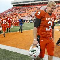 Photo -  OSU's Brandon Weeden walks off the field after OSU's 51-41 loos in the college football game between the Oklahoma State Cowboys (OSU) and the Nebraska Huskers (NU) at Boone Pickens Stadium in Stillwater, Okla., Saturday, Oct. 23, 2010. Photo by Bryan Terry, The Oklahoman ORG XMIT: KOD