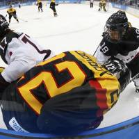 Photo - Yuka Hirano (17) and Tomoko Sakagami (18) of Japan battle up against the boards with Kerstin Spielberger of Germany during the 2014 Winter Olympics women's ice hockey game at Shayba Arena, Thursday, Feb. 13, 2014, in Sochi, Russia. (AP Photo/Petr David Josek)
