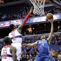 Photo - Minnesota Timberwolves guard Ricky Rubio (9), of Spain, goes to the basket against Washington Wizards guard John Wall (2) and Emeka Okafor (50) during the first half of an NBA basketball game on Friday, Jan. 25, 2013, in Washington. (AP Photo/Nick Wass)