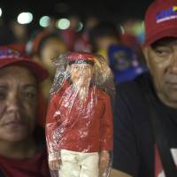 Photo - Supporters hold a doll depicting of the late President Hugo Chavez as they wait  in line to see his body outside the Fort Tiuna military academy in Caracas, Venezuela, Wednesday, March 6, 2013.  Chavez's body will lie in sate at the academy until his funeral, scheduled for Friday. (AP Photo/Esteban Felix)