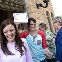 Photo - FILE - In this May 10, 2014 file photo, Kristin Seaton, center, of Jacksonville, Ark., holds up her marriage license as she leaves the Carroll County Courthouse in Eureka Springs, Ark., with her partner, Jennifer Rambo, left, of Fort Smith, Ark., in Eureka Springs, Ark. The Arkansas Supreme Court has rejected the state attorney general's request for a stay of a judge's ruling that overturned Arkansas' constitutional ban on gay marriage, Wednesday, May 14, 2014. (AP Photo/Sarah Bentham, file)