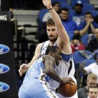 Photo - Denver Nuggets's J.J. Hickson, left, drives into Minnesota Timberwolves' Kevin Love in the first quarter of an NBA basketball game Wednesday, Feb. 12, 2014, in Minneapolis. (AP Photo/Jim Mone)