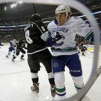 Photo - Vancouver Canucks ' Dale Weise, right, and Los Angeles Kings defenseman Drew Doughty (8) tangle in the first period of an NHL hockey game in Los Angeles, Monday, Jan. 13, 2014.  (AP Photo/Reed Saxon)