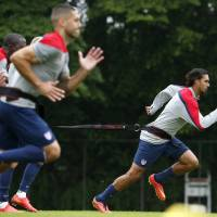 Photo - United States' Chris Wondolowski, right, runs resistance exercises with teammates, including Clint Dempsey, front, during a training session at the Sao Paulo FC training center in Sao Paulo, Brazil, Tuesday, June 10, 2014. The U.S. will play in group G of the 2014 soccer World Cup. (AP Photo/Julio Cortez)