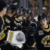Photo - Boston Bruins defenseman Torey Krug, right, celebrates his goal with bench teammates during the first period of an NHL hockey game against the Los Angeles Kings in Boston Monday, Jan. 20, 2014. (AP Photo/Elise Amendola)