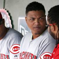 Photo - Cincinnati Reds starting pitcher Alfredo Simon, center, listens to starting pitcher Johnny Cueto, right, in the dugout during the fourth inning of a baseball game against the Washington Nationals at Nationals Park Wednesday, May 21, 2014, in Washington. (AP Photo/Alex Brandon)