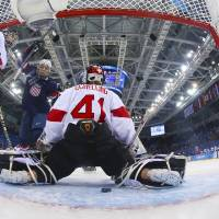 Photo - Hilary Knight of the Untied States celebrates as the puck slides past Goalkeeper Florence Schelling of Switzerland for a goal during the first period of the women's ice hockey game at the 2014 Winter Olympics, Monday, Feb. 10, 2014, in Sochi, Russia. (AP Photo/Bruce Bennett, Pool)