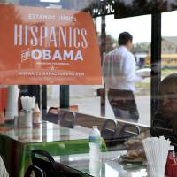 Photo -   FILE - In this Oct. 26, 2012, file photo, Spanish language election campaign signs promoting President Barack Obama hang on the windows at Lechonera El Barrio Restaurant in Orlando, Fla. Hispanics supported President Barack Obama over Republican Mitt Romney by almost 3-to-1 and put Republicans on notice they must take real steps to win over the nation's largest minority group if they want to win the presidency again. Exit polls say that Romney, who has backed hardline immigration measures, won only 27 percent of Hispanics. (AP Photo/Julie Fletcher)