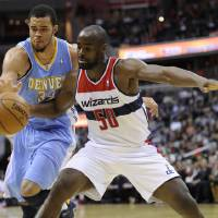 Photo - Washington Wizards center Emeka Okafor (50) works for the ball against Denver Nuggets center JaVale McGee (34) during the second half of an NBA basketball game, Friday, Feb. 22, 2013, in Washington. The Wizards won 119-113. (AP Photo/Nick Wass)