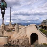 Photo - This September 2013 photo shows a structure in Tres Piedras, a colony of self-sustaining homes near Taos, N.M., that look like spaceships embedded in the scenic landscape. The 70 homes are made from all recycled materials and the community is headquarters of one of the early leaders in the sustainable building movement, Earthship Biotecture. The community is one of a number of attractions in the Taos area that won't cost visitors a dime. (AP Photo/Erica Asmus-Otero)