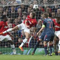 Photo - Manchester United's Nemanja Vidic, center, scores the opening goal during the Champions League quarterfinal first leg soccer match between Manchester United and Bayern Munich at Old Trafford Stadium, Manchester, England, Tuesday, April 1, 2014.(AP Photo/Jon Super)