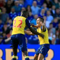 Photo - Arsenal's Alexis Sanchez, right, celebrates scoring his side's first goal of the game with teammate Yaya Sanogo during their English Premier League soccer match against Leicester City at the King Power Stadium, Leicester, England, Sunday, Aug. 31, 2014. (AP Photo/Nick Potts, PA Wire)     UNITED KINGDOM OUT    -   NO SALES   -   NO ARCHIVES