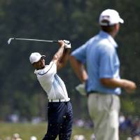 Photo - Tiger Woods hits from the fairway on the second hole as Steve Stricker looks on during a practice round for the PGA Championship golf tournament at Valhalla Golf Club on Wednesday, Aug. 6, 2014, in Louisville, Ky. The tournament is set to begin on Thursday. (AP Photo/David J. Phillip)