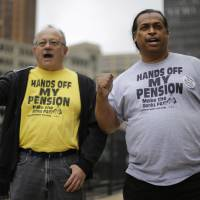 Photo - FILE - In a Thursday, July 3, 2014 file photo, Detroit retirees Mike Shane, left, and William Davis protest near the federal courthouse in Detroit. Workers and retirees approved pension cuts in Detroit's bankruptcy by a landslide, the city reported Monday, a crucial step to emerging from the largest municipal insolvency in U.S. history. The city disclosed results from two months of balloting, which ended July 11. Judge Steven Rhodes still must hold a trial in August to determine if Detroit's overall bankruptcy plan is fair and feasible to all creditors, from Wall Street to Main Street, but support from retirees is vital. (AP Photo/Paul Sancya, File)