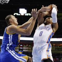 Photo -   Oklahoma City Thunder guard Russell Westbrook (0) shoots as Golden State Warriors center Andris Biedrins, left, defends, in the first quarter of an NBA basketball game in Oklahoma City, Sunday, Nov. 18, 2012. (AP Photo/Sue Ogrocki)