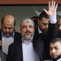 Photo - File - In this Dec. 9, 2012 file photo, Hamas leader Khaled Mashaal waves during his visit to the Islamic University in Gaza City. Hamas chief Khaled Mashaal has set an ambitious agenda for his new term, seeking to transform his once isolated Islamic militant movement into a widely recognized political force, without making concessions toward Israel needed for international acceptance. (AP Photo/Hatem Moussa, File)
