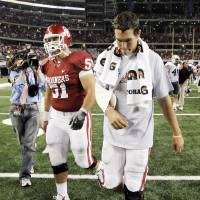 Photo - SHOULDER INJURY: OU quarterback Sam Bradford walks off the field next to Brian Lepak (51)  after the college football game between the Brigham Young University Cougars (BYU) and the University of Oklahoma Sooners (OU) at Cowboys Stadium in Arlington, Texas, Saturday, September 5, 2009. Bradford was injured near the end of the first half and did not play in the rest of the game. BYU won, 14-13. By Nate Billings, The Oklahoman ORG XMIT: KOD