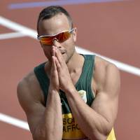 Photo - FILE - This is a Saturday, Aug. 4, 2012 file photo of South Africa's Oscar Pistorius  as he reacts after finishing first in a men's 400-meter heat during the athletics in the Olympic Stadium at the 2012 Summer Olympics, London  Paralympic superstar Oscar Pistorius was charged Thursday Feb. 14. 2013 with the murder of his girlfriend who was shot inside his home in South Africa, a stunning development in the life of a national hero known as the Blade Runner for his high-tech artificial legs. (AP Photo/Martin Meissner, File)