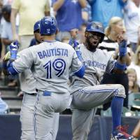 Photo - Toronto Blue Jays' Jose Bautista (19) celebrates hiS three-run home run with teammate Jose Reyes during the sixth inning of a baseball game against the Milwaukee Brewers Wednesday, Aug. 20, 2014, in Milwaukee. (AP Photo/Morry Gash)
