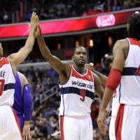Photo - Washington Wizards forward Martell Webster (9) reacts with teammates Garrett Temple (17) and Nene (42), of Brazil, during the second half of an NBA basketball game against the Phoenix Suns, Saturday, March 16, 2013, in Washington. The Wizards won 127-105. (AP Photo/Nick Wass)