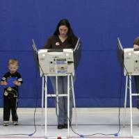 Photo -   Amy Deming, left, casts her ballot as her son Max, 4, plays with his V-Reader and Wendy Watt, right, votes at Pony Express Elementary School in Eagle Mountain, Utah, Tuesday, Nov. 6, 2012. (AP Photo/The Salt Lake Tribune, Rick Egan) DESERET NEWS OUT; LOCAL TV OUT; MAGS OUT