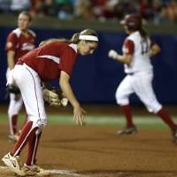 Photo - OU's Kelsey Stevens turns around after giving up a two-run home run to Alabama's Jadyn Spencer, at right, in the fifth inning of a Women's College World Series game between at ASA Hall of Fame Stadium in Oklahoma City Thursday, May 29, 2014. Photo by Bryan Terry, The Oklahoman