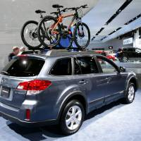Photo - Bicycles are shown as accessories on the Suburu Outback wagon at the North American International Auto Show in Detroit, Wednesday, Jan. 16, 2013. Transportation of the two-wheeled variety is sharing the floor at the auto show in Detroit along with the latest cars, trucks and concept vehicles. Bikes weren't the focus of presentations during this week's press previews, but they're often used in marketing cars. (AP Photo/Paul Sancya)