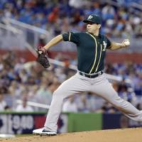 Photo - Oakland Athletics' Tommy Milone delivers a pitch during the first inning of a baseball game against the Miami Marlins, Sunday, June 29, 2014 in Miami. (AP Photo/Wilfredo Lee)