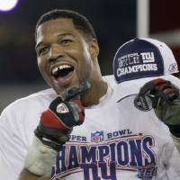 Photo - FILE - In this Feb. 3, 2008, file photo, New York Giants defensive end Michael Strahan celebrates after the Giants defeated the New England Patriots 17-14 in the Super Bowl XLII football game in Glendale, Ariz. While Strahan was a game-changer on the field, he was making his mark elsewhere with his gregarious personality, gap-toothed smile and willingness to step out of his comfort zone. He became a regular in commercials,  (AP Photo/David J. Phillip, File)