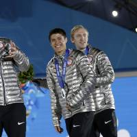 Photo - The team from the United States, who won the silver medal in the men's short track speedskating 5,000-meter relay, smile while exiting the stage following their medals ceremony at the 2014 Winter Olympics, Saturday, Feb. 22, 2014, in Sochi, Russia. (AP Photo/David Goldman)