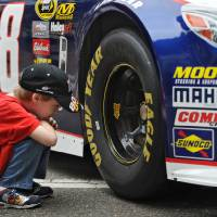 Photo - Daniel Clark, 6, wearing a Clint Bowyer t-shirt gets an up close look at the new Gen6 Chevrolet SS No 88 car of Dale Earnhardt Jr. during NASCAR day Tuesday, Feb. 12, 2013, in Jacksonville, Fla.  The event is part a multi-city media blitz introducing the 2013 NASCAR Sprint Cup Series Chevrolet SS, Ford Fusion and Toyota Camry race cars.  (AP Photo/The Florida Times-Union, Bob Mack) MAGS OUT. TV OUT