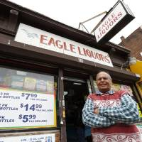 Photo - Store employee Pravin Mankodia stands outside Eagles Liquors in Passaic, N.J. Monday, March 25, 2013. Mankodia sold the winning $338 million Powerball ticket that was claimed by an unidentified New Jersey Resident. (AP Photo/Rich Schultz)