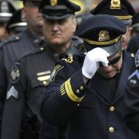 Photo - A Revere, Mass. police captain holds his cap while entering a memorial service for fallen Massachusetts Institute of Technology police officer Sean Collier, in Cambridge, Mass., Wednesday, April 24, 2013. Collier was fatally shot on the MIT campus Thursday, April 18, 2013. Authorities allege that the Boston Marathon bombing suspects were responsible. (AP Photo/Steven Senne)