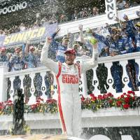 Photo - Dale Earnhardt Jr. celebrates after winning the NASCAR Sprint Cup Series Pocono 400 auto race at Pocono Raceway on Sunday, June 8, 2014, in Long Pond, Pa. (AP Photo/Mike Groll)