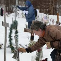Photo - Tonda Daniels, of South Kingstown, R.I., front, places an ornament on a makeshift memorial to her fallen sister Lori Durante at the site of the Station nightclub fire, Sunday, Feb. 17, 2013, in West Warwick, R.I. The Station Fire Memorial Foundation unveiled final plans to build a permanent memorial at the site during ceremonies Sunday. The 2003 blaze took the lives of 100 people. (AP Photo/Steven Senne)