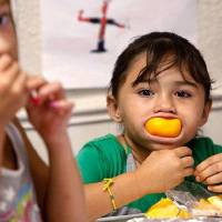 Photo - Miracle Medrano, 7, enjoys an orange slice, while a friend, Cristal (cq) Ramirez, 8, also enjoys an orange.   JIM BECKEL - THE OKLAHOMAN