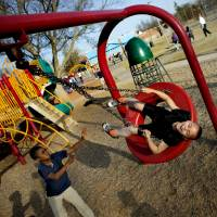 Photo - Randy Green, 6, laughs as Navy Hill, 8, pushes him in a tire swing at the Boys and Girls Club. Photo by Bryan Terry, The Oklahoman