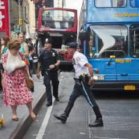 Photo - A woman, her arm bandaged and in a sling, leaves after being treated at the scene of a traffic accident apparently involving two double-decker tour buses in New York's Times Square, Tuesday Aug. 5, 2014.  The Fire Department of New York says 11 people suffered injuries, three of them seriously, but none of the injuries is believed to be life-threatening. (AP Photo/Bebeto Matthews)