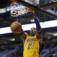 Photo - Los Angeles Lakers' Dwight Howard dunks against the Phoenix Suns during the first half on an NBA basketball game, Wednesday, Jan. 30, 2013, in Phoenix. (AP Photo/Matt York)