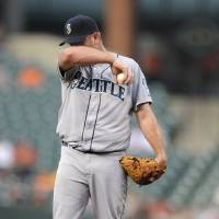 Photo -   Seattle Mariners starting pitcher Kevin Millwood wipes his face during the first inning of a baseball game against the Baltimore Orioles, Wednesday, Aug. 8, 2012, in Baltimore. (AP Photo/Nick Wass)