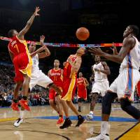 Photo - Oklahoma CIty's Thabo Sefolosha passes the ball to Kevin Durant between Houston's Kyle Lowry, left, and Kevin Martin during the NBA basketball game between the Oklahoma City Thunder and the Houston Rockets at the Oklahoma City Arena on Wednesday, December 15,  2010.   Photo by Bryan Terry, The Oklahoman