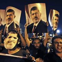 Photo - In this Wednesday, July 10, 2013 photo, supporters of ousted Egypt's President Mohammed Morsi, hold posters of him as they protest during the Islamic month of Ramadan, in Nasr City, Cairo, Egypt. As the sun set on the first day of the Islamic holy month of Ramadan, families across Cairo gathered for the fast-breaking iftar meal in a country that in the last two weeks has seen protests by millions, a coup against an elected president and the deaths of dozens of people in clashes with the military. Ramadan is traditionally a time of personal reflection and feeling a sense of brotherhood with fellow Muslims, but in the aftermath of the military overthrow of President Mohammed Morsi, the divisions among Egyptians extend even down to this traditional meal. (AP Photo/Hussein Malla)