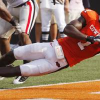 Photo - Dez Bryant falls into the end zone after a catch during the college football game between OSU and the University of Georgia at Boone Pickens Stadium on the campus of Oklahoma State University in Stillwater Saturday, Sept. 5, 2009. Photo by Doug Hoke, The Oklahoman. ORG XMIT: KOD