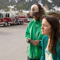 Photo - Kristin Livingstone, right, watches her evacuated hillside neighborhood after spending a night away from her home because of danger from a potential landslide in Jackson, Wyo., Thursday, April 10, 2014. Brendon Newton, left, gets in touch with others at an assembly point in a parking lot across the street from the threatened slope. Dozens of Jackson residents who were evacuated after land began shifting on the hillside. (AP Photo/Jackson Hole News & Guide, Angus M. Thuermer Jr.)