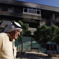 Photo -   In a Tuesday, June 5, 2012 photo, Syrian Abu Eissa Ghazzal, 75, walks next to a house that was burned during a military operation by the Syrian army in April 2012, in the town of Taftanaz, 15 kilometers east of Idlib, Syria. At dawn on April 3, Syrian forces shelled the town in the first volley of what residents say was a massive assault after a string of large protests calling for the end of the autocratic rule of President Bashar Assad. (AP Photo/Khalil Hamra)